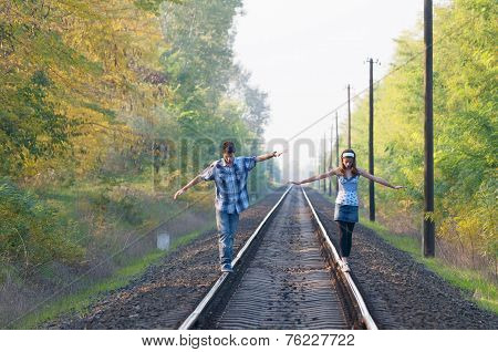 Teen Girl And Boy Balancing On Rails