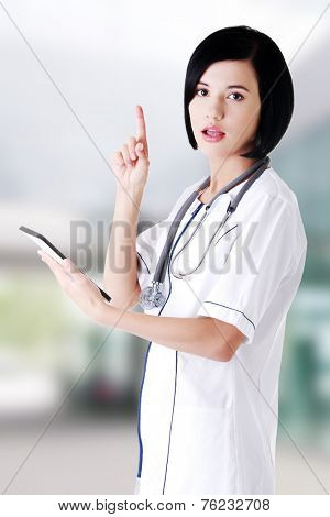 Female doctor using tablet computer and pointing on copy space