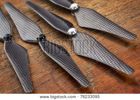 set  of four carbon fiber self-tightening propellers for a quadcopter drone against grunge wood