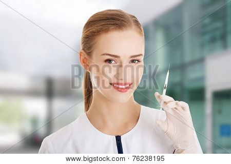 Beautiful young doctor or nurse is holding a needle. Isolated on white.