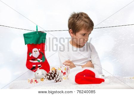 Portrait of sad boy with Christmas decorations.