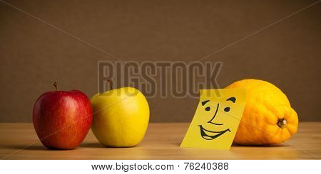 Lemon with sticky post-it note looking at apples