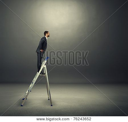 smiley businessman standing on the stepladder and looking at empty copyspace. photo in the dark room