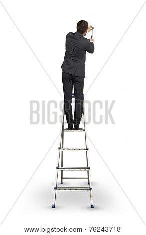 businessman standing on the stepladder and hitting nail into the wall. isolated on white background