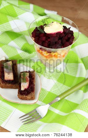Russian herring salad in glass bowl and sandwiches with salted herring, on wooden table background