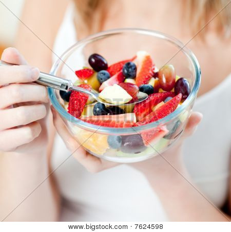 Close-up Of A Woman Eating A Fruit Salad
