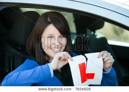 Jolly Teen Girl Sitting In Her Car Tearing A L-sign