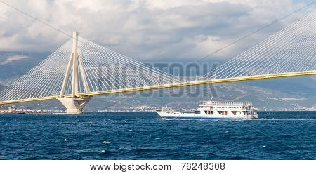 Ferry Boat Sailing Under Suspension Bridge