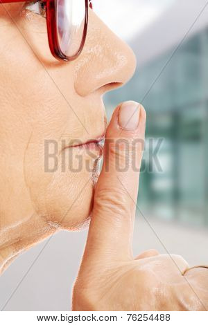 Elderly woman is having finger on her lips