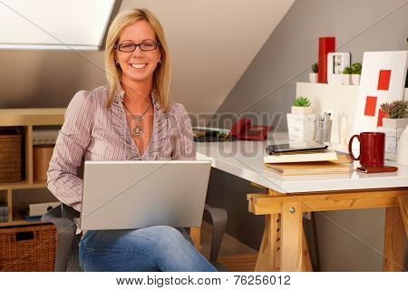 Happy woman holding laptop computer on lap, sitting at home, smiling, looking at camera.