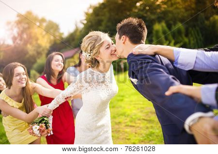 Newlyweds kissing in park