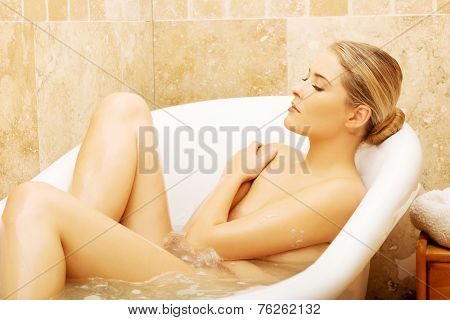 Beautiful woman relaxing in bathtub with her eyes closed.