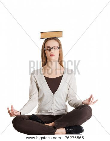 Woman sitting cross-legged holding book on head.