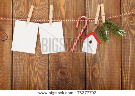 Snow fir tree, photo frame and christmas decor on rope over rustic wooden board with copy space