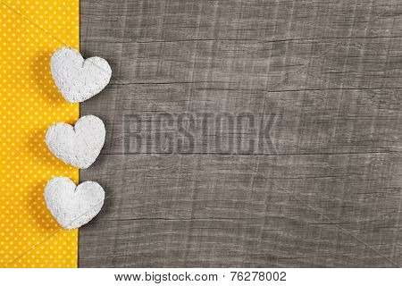 Wooden background with three white and yellow hearts on wooden brown old background with polka dots.