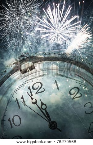 New Year's at midnight - Old clock against fireworks