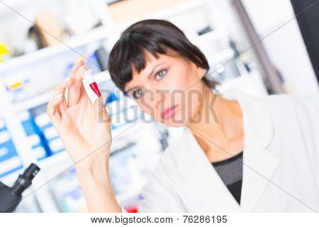 woman in a laboratory with microtube test tube  in hand and PCR centrifuge