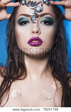 Beautiful brunette mermaid woman with creative make up and jewelry on her wet hairstyled head