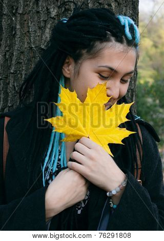Close up Braided Hair Pretty Woman Covering her Face with Yellow Autumn Leaf While Leaning on the Tree Trunk.