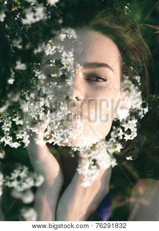 Double exposure portrait of elegant woman combined with photograph of white flowers