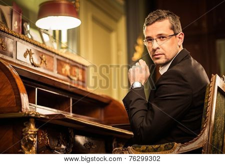 Confident middle-aged man in luxury vintage style interior
