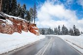 stock photo of slippery-roads  - Empty snow covered road in winter landscape - JPG