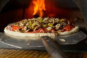 picture of hot fresh pizza  - Fresh original Italian pizza on a shovel is putting in a traditional wood - JPG