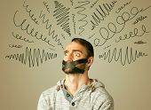 stock photo of taboo  - Young man with taped mouth and curly lines around his head   - JPG
