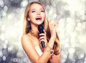 foto of singer  - Beauty model girl singer with a microphone singing and dancing over holiday glowing background - JPG