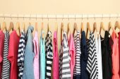 stock photo of clothes hanger  - Colorful clothes on hangers in room - JPG