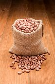 stock photo of phaseolus  - Loose dry pinto beans in burlap sack on wooden board background - JPG