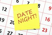image of life event  - The phrase Date Night on a yellow sticky note attached to a calendar as a reminder of a special event - JPG