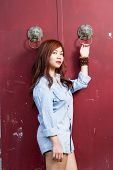 pic of filipina  - Asian woman in front of traditional Chinese door with ornate lion head knockers - JPG
