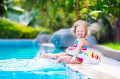 pic of girl toy  - Adorable little girl with curly hair wearing a colorful swimming suit playing with water splashes at beautiful pool in a tropical resort having fun during family summer vacation - JPG