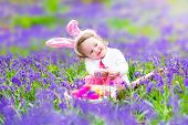 stock photo of bunny ears  - Adorable toddler girl with bunny ears having fun at Easter egg hunt in a beautiful forest with first spring flowers - JPG
