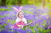 foto of easter eggs bunny  - Adorable toddler girl with bunny ears having fun at Easter egg hunt in a beautiful forest with first spring flowers - JPG
