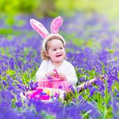 pic of bunny ears  - Adorable toddler girl with bunny ears having fun at Easter egg hunt in a beautiful forest with first spring flowers - JPG