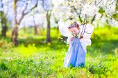 stock photo of fairies  - Adorable toddler girl with curly hair and flower crown wearing a magic fairy costume with a blue dress and angel wings playing in a sunny blooming fruit garden with cherry blossom and apple trees - JPG