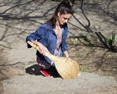 stock photo of sweeper  - Portrait of young woman sweeps with a sweeper garbage outdoor - JPG