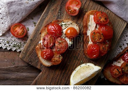 Slices of white toasted bread with canned tomatoes and lime on cutting board on wooden table background
