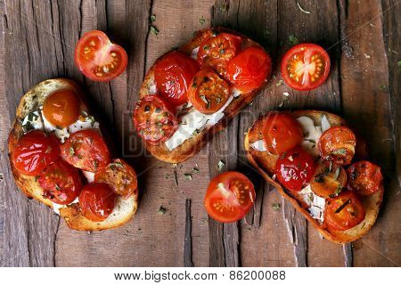 Slices of white toasted bread with butter and canned tomatoes on wooden table background