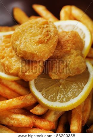 Breaded fried chicken nuggets and potatoes with sliced lemon, macro view