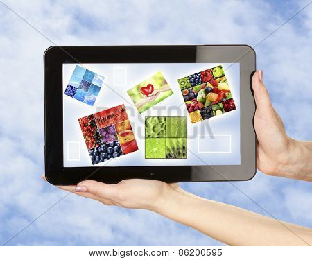 Touch screen tablet with beautiful images on sky background