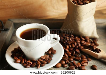 Cup of coffee with beans on tray and rustic wooden background