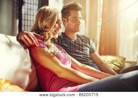 couple watching something at home with lens flare and warm tone to image