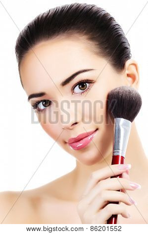 Beautiful girl with a makeup brush, white background, isolated