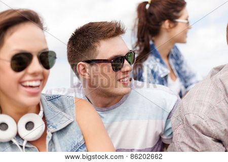 summer holidays and teenage concept - group of teenagers hanging outside