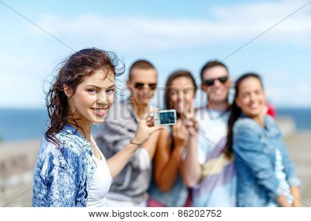 summer holidays and teenage concept - group of happy teenagers taking photo outside