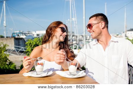love, dating, people and food concept - smiling couple wearing sunglasses eating dessert and looking to each other at cafe