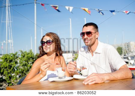 love, dating, people and food concept - smiling couple wearing sunglasses eating dessert at cafe